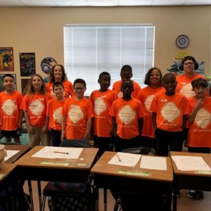 class photo of elementary age students all in orange shirts