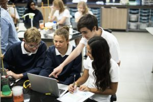 Four students working together around laptop in science classroom