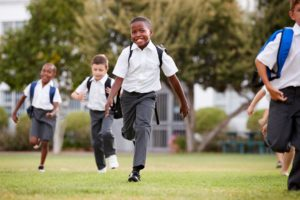 Young students in uniforms running happily toward camera across lawn